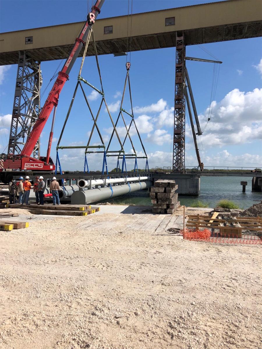 Cranes lifting pipes